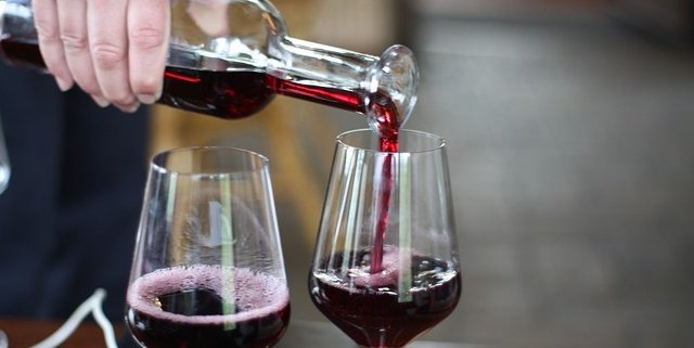 Wine being poured from a bottle into two glasses