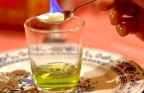 glass with absinthe and hand holding Absinthe spoon with a flaming sugar cube over the top