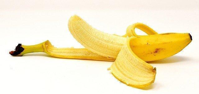 half peeled banana laying on its side on a white background to illustrate banana aphrodisiac