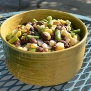 two bean salad in a yellow bowl on a blue, metal table