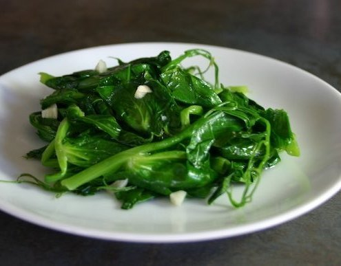 closeup of garlicky pea tendrils on a white plate