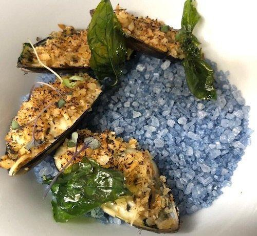 Closeup of Mussels Dish on grey salt from She restaurant Cancun