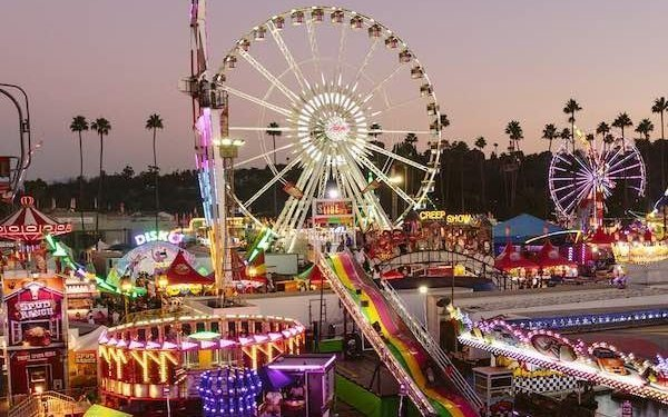 Sunset image of a romantic date at the LA County Fair ferris wheel and other ride attractions
