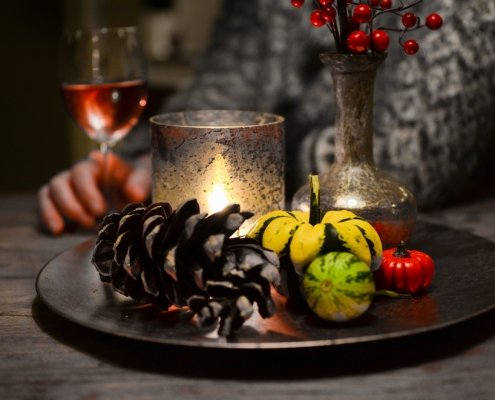 pinecone and candle still life in foreground with woman in a grey sweater drinking rosé in the background to illustrate our wine pairing with turkey article for Thanksgiving