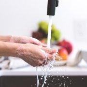 scrubbing hands at the kitchen sink