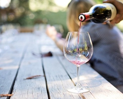 person pouring wine at picnic table