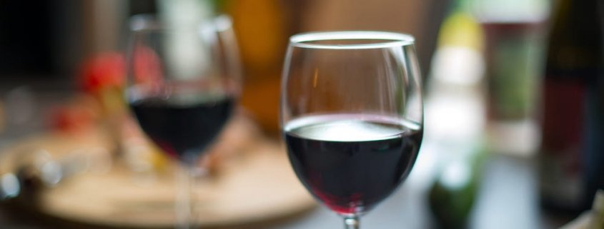 Two glasses of Syrah on a dark table