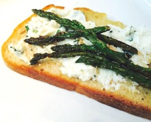 Asparagus & Ricotta Toast with Avocado Oil on a white plate