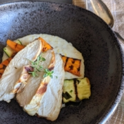 creamy polenta with grilled chicken and vegetables in a black bowl with a silver serving spoon and tan napkin