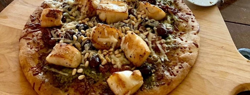 homemade scallop pizza on a wooden board