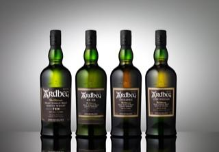 Four bottles of Scotch on a grey background