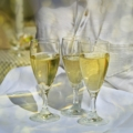 several types of white wine in stemmed glasses against a white backgroung