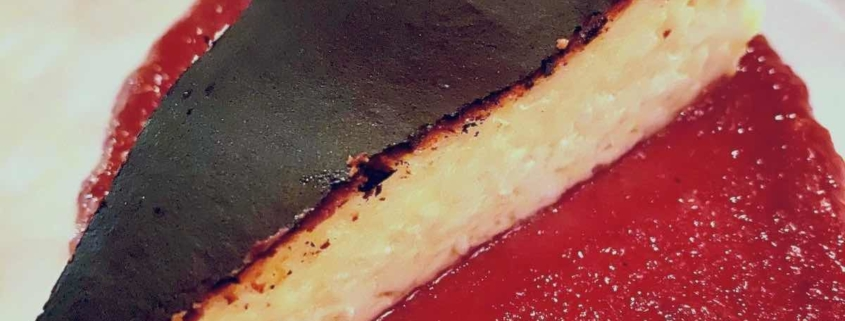 Burnt Basque Cheesecake with a red sauce on a white plate