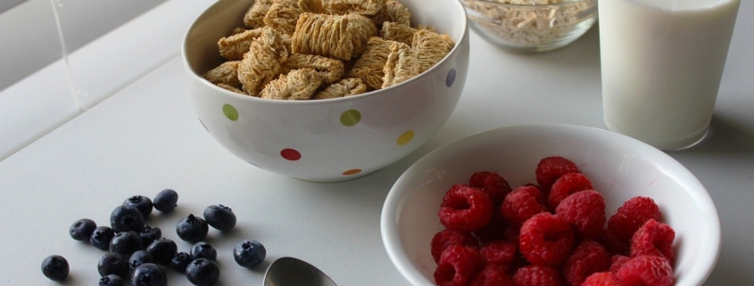 breakfast tray with berries and whole grains, glass of milk