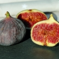 two figs, one cut in half as an illustration of the benefits of figs