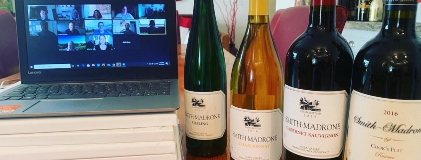 computer open to a Zoom wine tasting with a lineup of wine bottles beside it