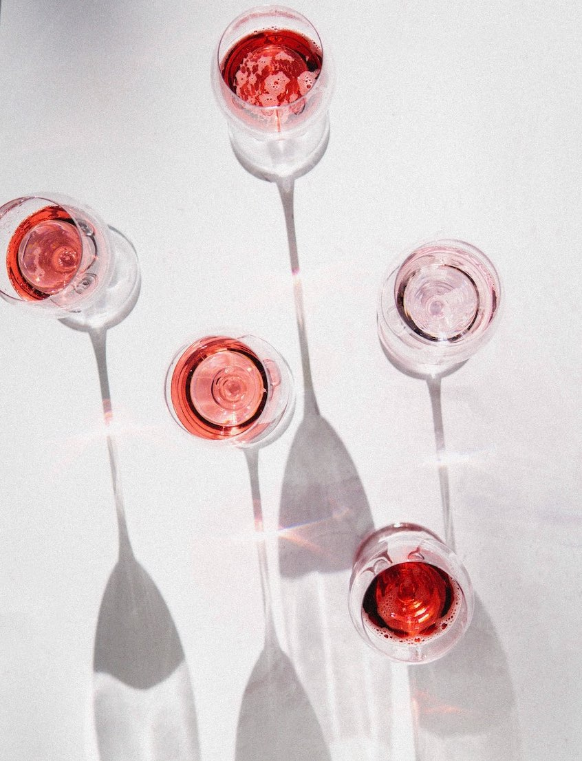 a wine tasting with glasses of rose wine on a white background