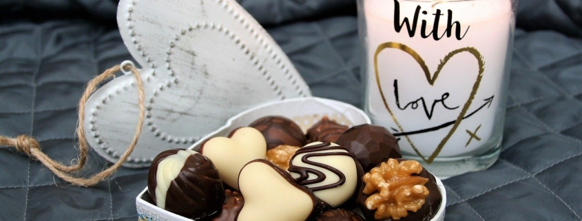 chocolate aphrodisiac image of chocolates in a white, heart-shaped box with a candle flickering in the background