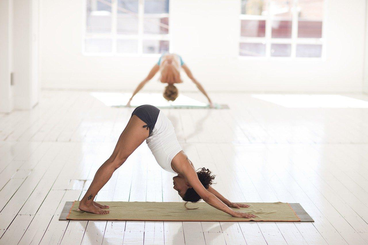 two women practicing yoga in a studio