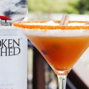 pumpkin apple cider cocktail in a martini glass with a bottle of Broken Shed vodka in the background