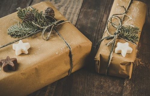 2 packages with brown paper wrapping, greenery and cookies to illustrate our 2020 gift guide