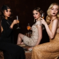 Three women in evening gowns drinking Champagne while sitting on a bar