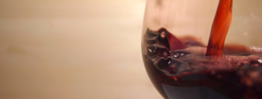 red wine being poured into a pinot noir glass