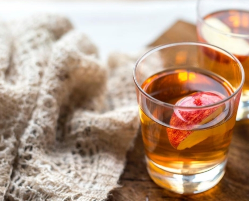 closeup of hot apple cider cocktail next to a knit beige blanket on a wooden table