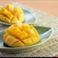 Two half mango on leaf-shaped plates