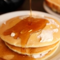 maple syrup poured onto pancakes with butter