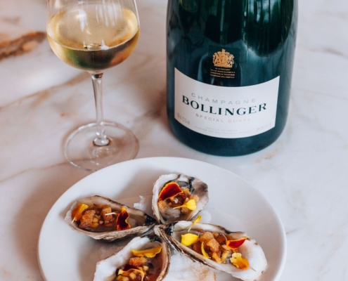 Bollinger Special Cuvee bottle on a white tablecloth with a plate of oysters