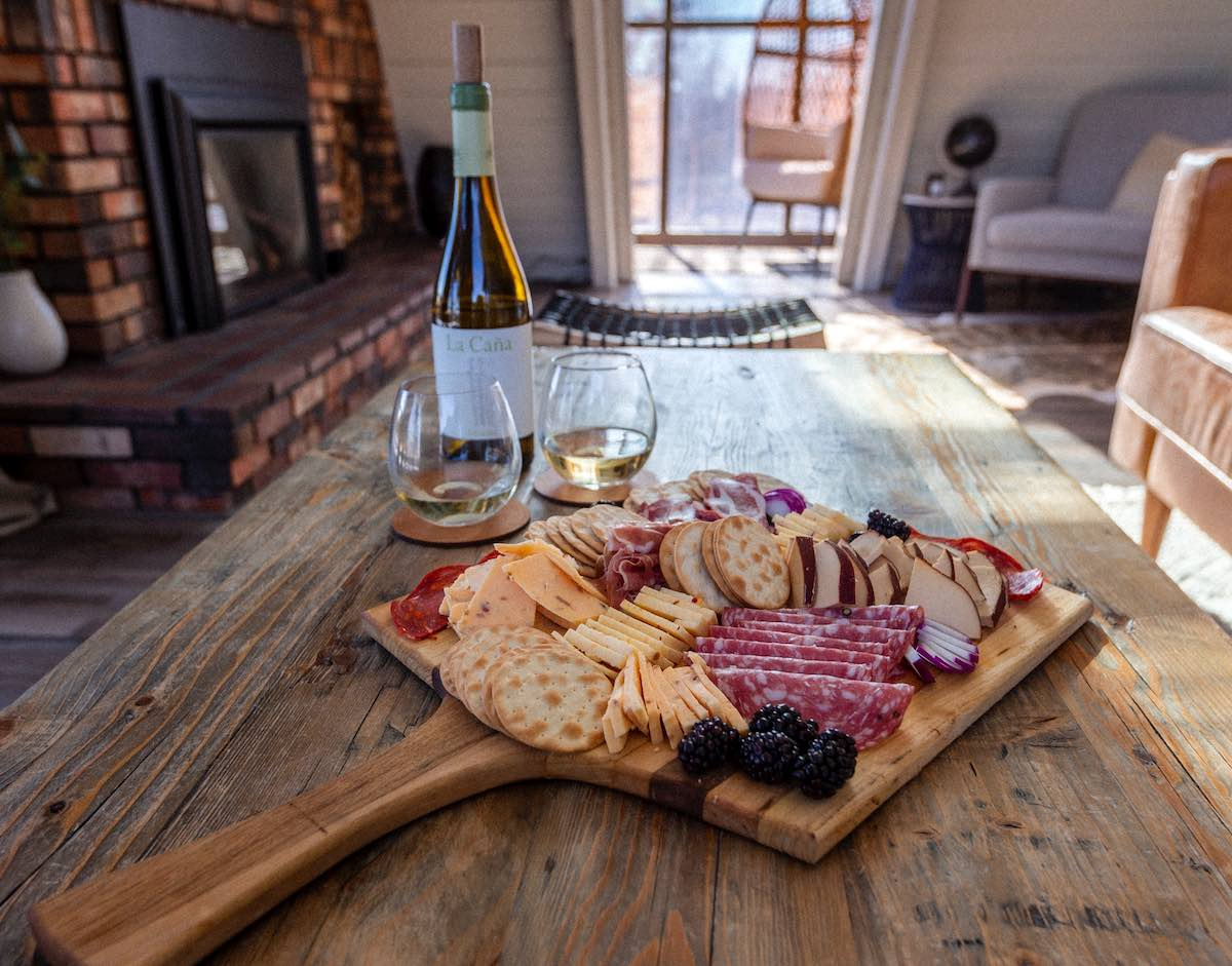 example of a charcuterie board to buy on a wooden table with a bottle of wine