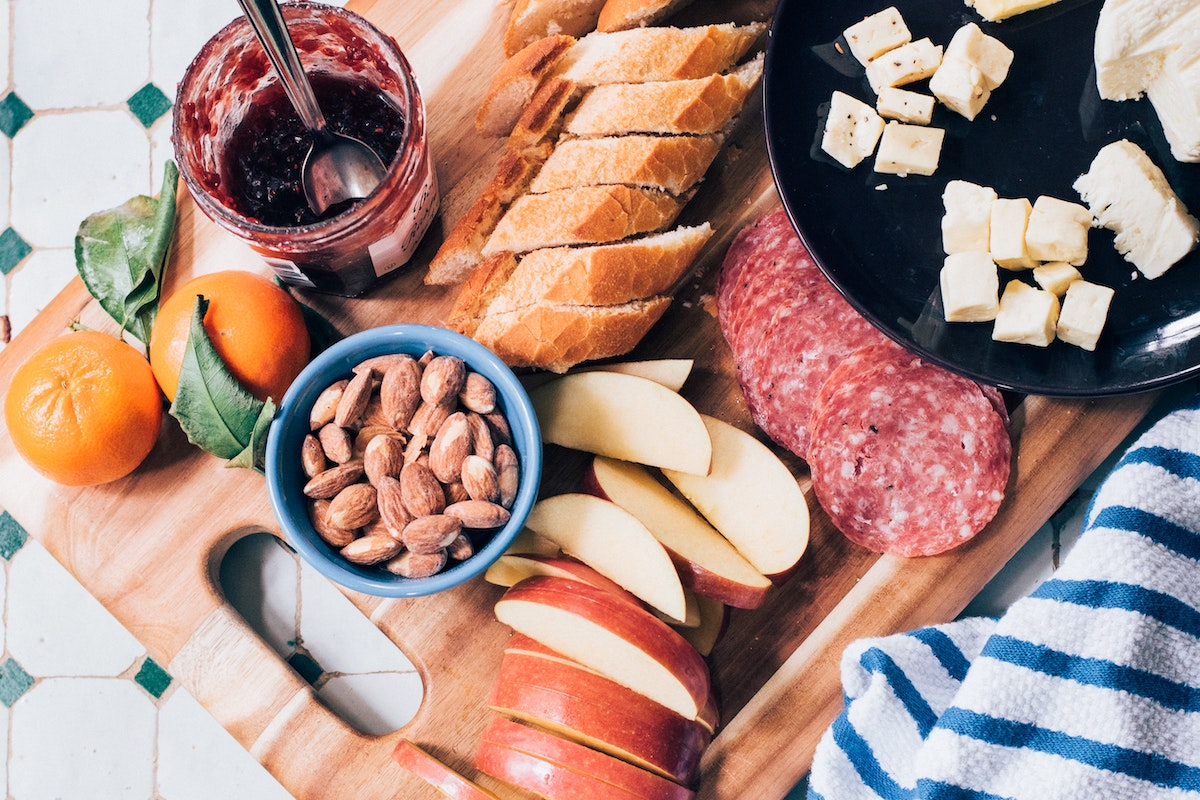 A traditional charcuterie board with sliced baguette, saussicon, apple slices, nuts and blueberry jam