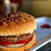 bison burger (buffalo burger) with a whole wheat bun on a white plate with a red heart
