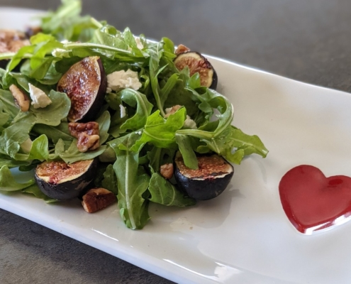 grilled fig and arugula salad on a white plate with a red heart