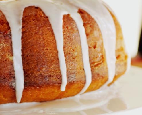 closeup of pumpkin bundt cake with a vanilla glaze on a white plate