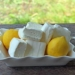closeup of a pile of lemon marshmallows on a plate with two fresh lemons