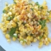 closeup of corn salad with finger lime and wild arugula on a white plate